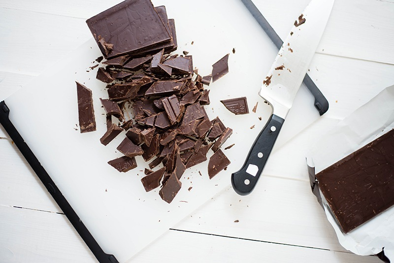 Overhead view of a bar of dark chocolate, chopped and ready to go into a healthy benefits recipe.