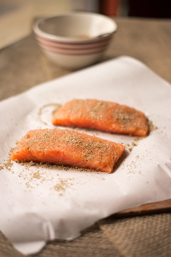Spice-rubbed raw salmon fillets with their skin on, ready to make pan-fried salmon dish