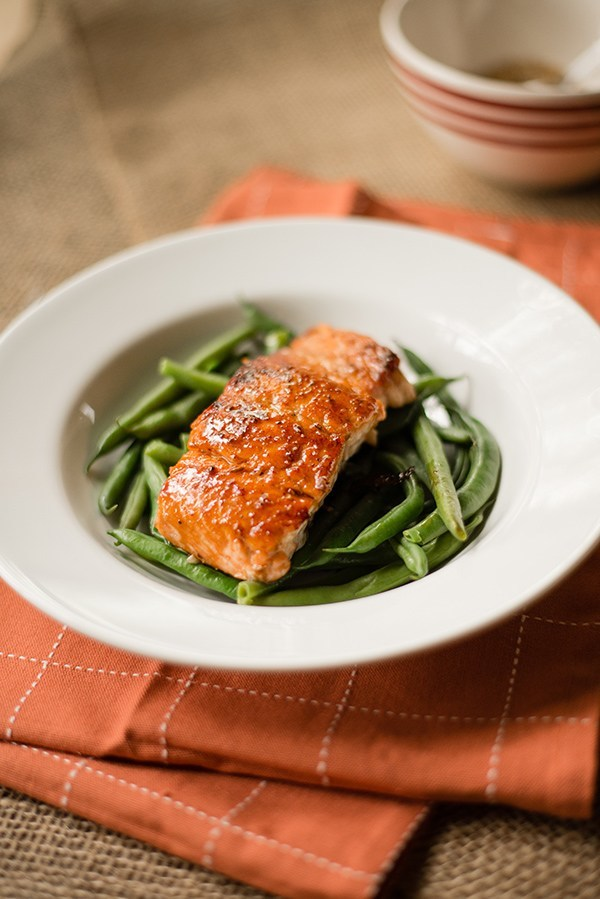Single fillet of salmon that has been pan fried and is plated over garlic parmesan green beans. The spice rub for the pan fried salmon can be seen in the background.