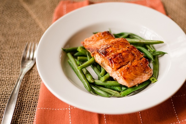 Close up of pan-cooked salmon on a bed of green beans, ready to be served and enjoyed