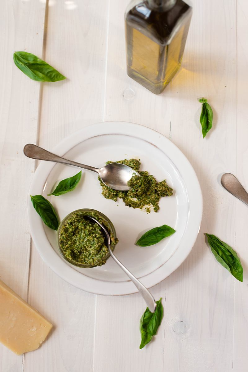 Overhead view if a small bowl of Healthy Pesto Sauce on a white plate, with a spoon of pesto off to the side.