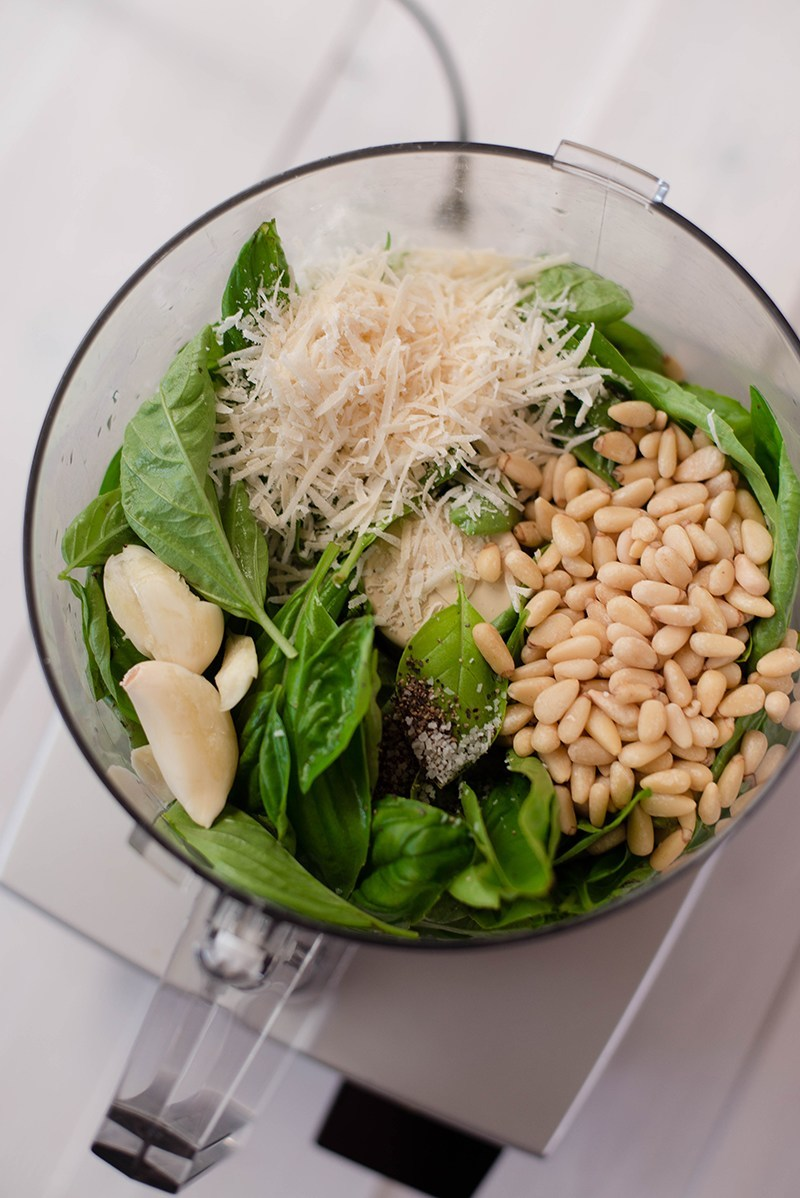 Overhead view of Pesto Sauce ingredients in the food processor, including grated parmesan cheese, pine nuts, basil, and garlic.