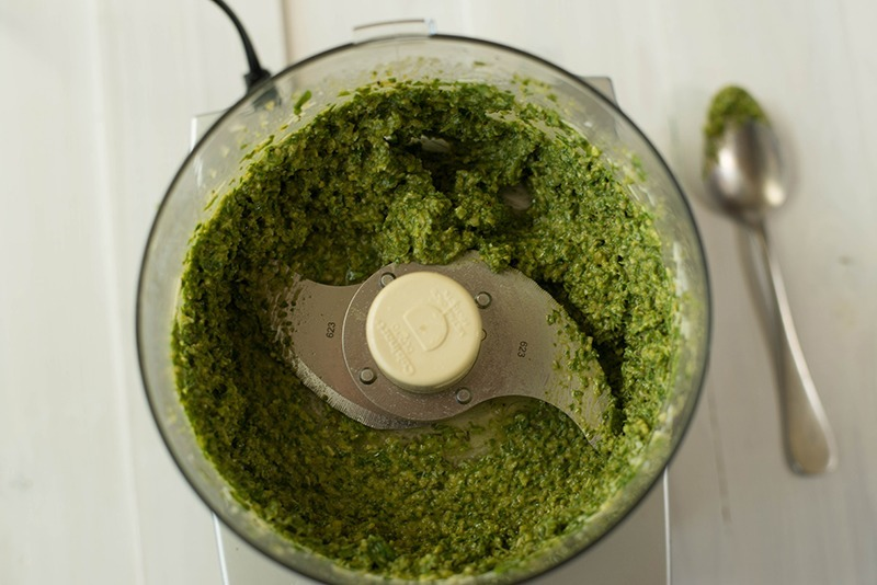 Overhead view of the food processor containing ready to serve pesto sauce.