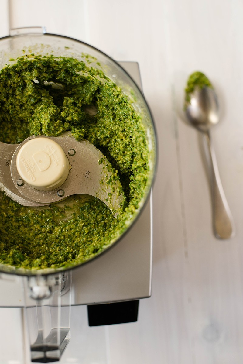 Overhead view of the food processor containing pesto sauce, processed and ready to serve.