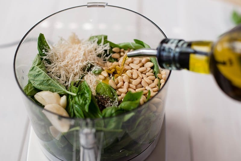 Close up view of Pesto Sauce ingredients in the food processor and the oil being poured in, ready to blend.