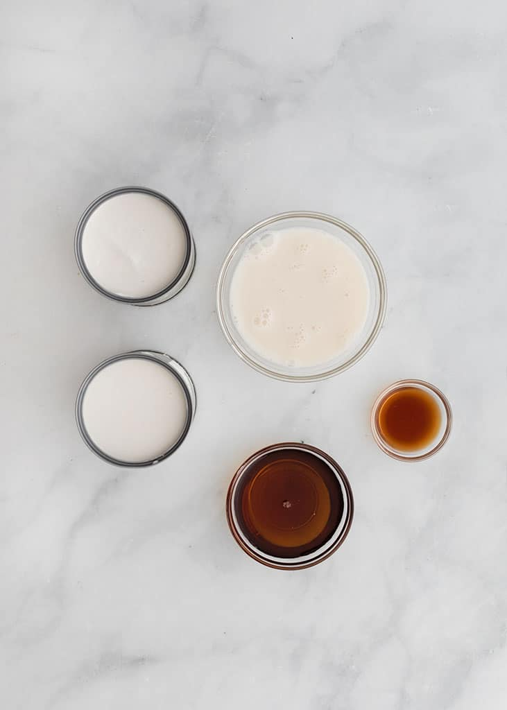 Overhead image of the ingredients for Healthy Vanilla Ice Cream including coconut milk, pure maple syrup and pure vanilla.