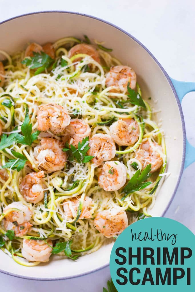Overhead view of a dish filled with Healthy Shrimp Scampi and including zucchini noodles, parmesan, and Italian parsley.