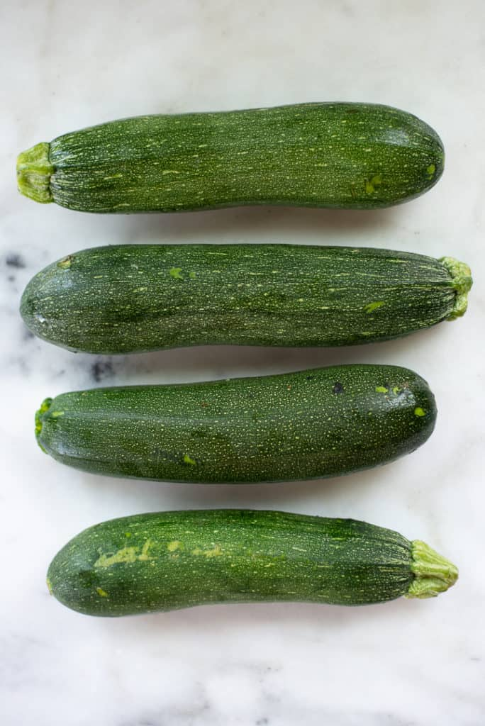 Overhead close up image of 4 zucchinis, whole and unpeeled, lying on the counter.