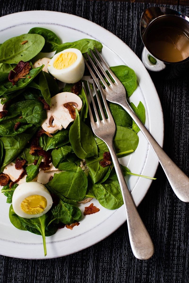 Close up view of Spinach Salad With Warm Bacon Dressing topped with boiled eggs and mushrooms, on a white plate with two forks.