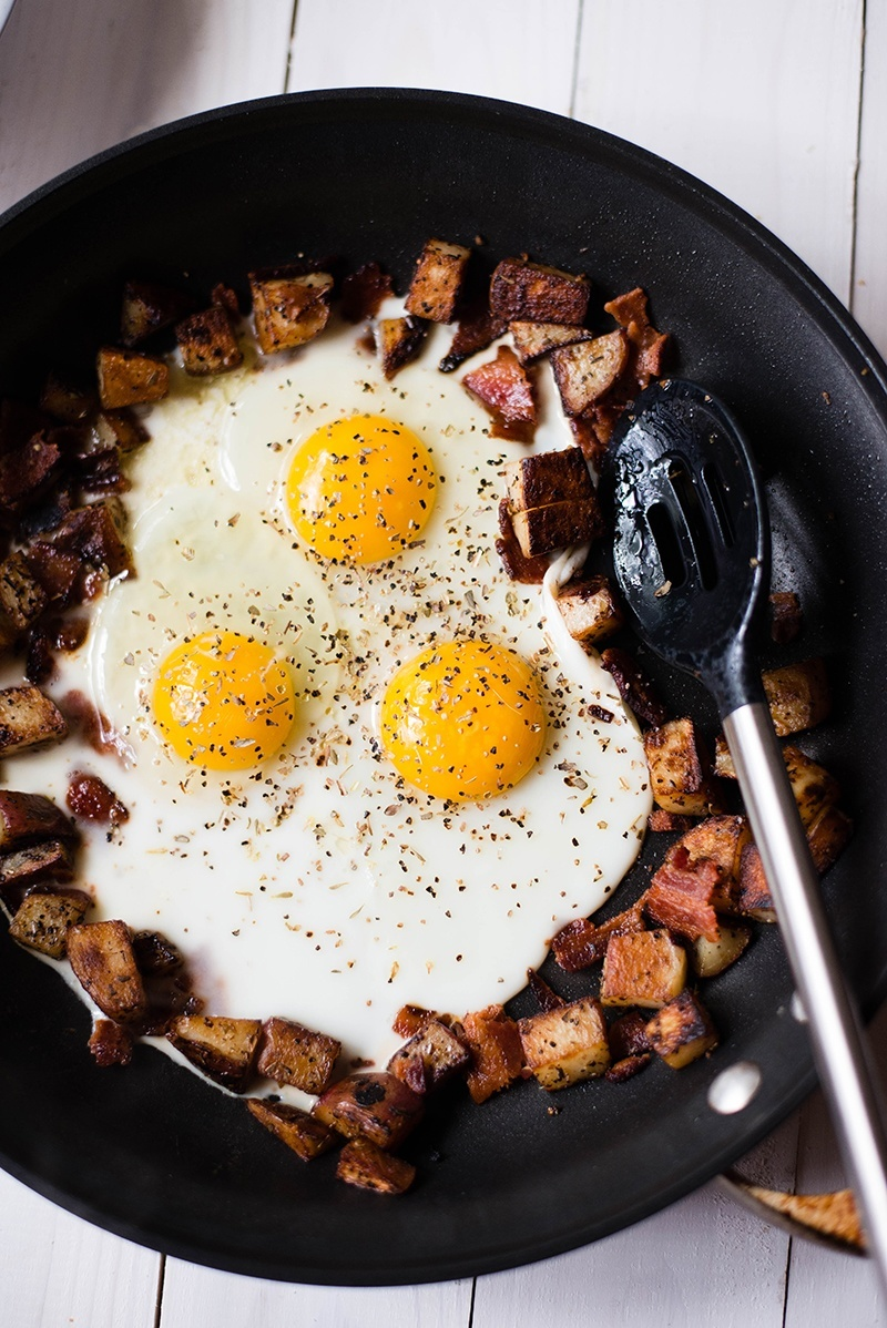 Overhead image of eggs being added to a homemade burrito mix in a cast iron pan, an example of a meal that lowers blood sugar.
