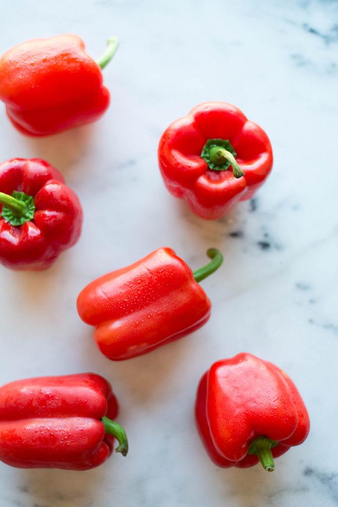 Overhead image of 6 whole red bell peppers, a low carb veggie ideal to incorporate into a low carb meal.
