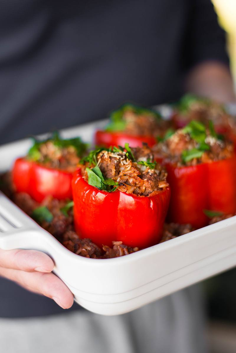 Man holding casserole dish filled with baked stuffed bell peppers, fresh from the oven, and topped with fresh italian parsley.
