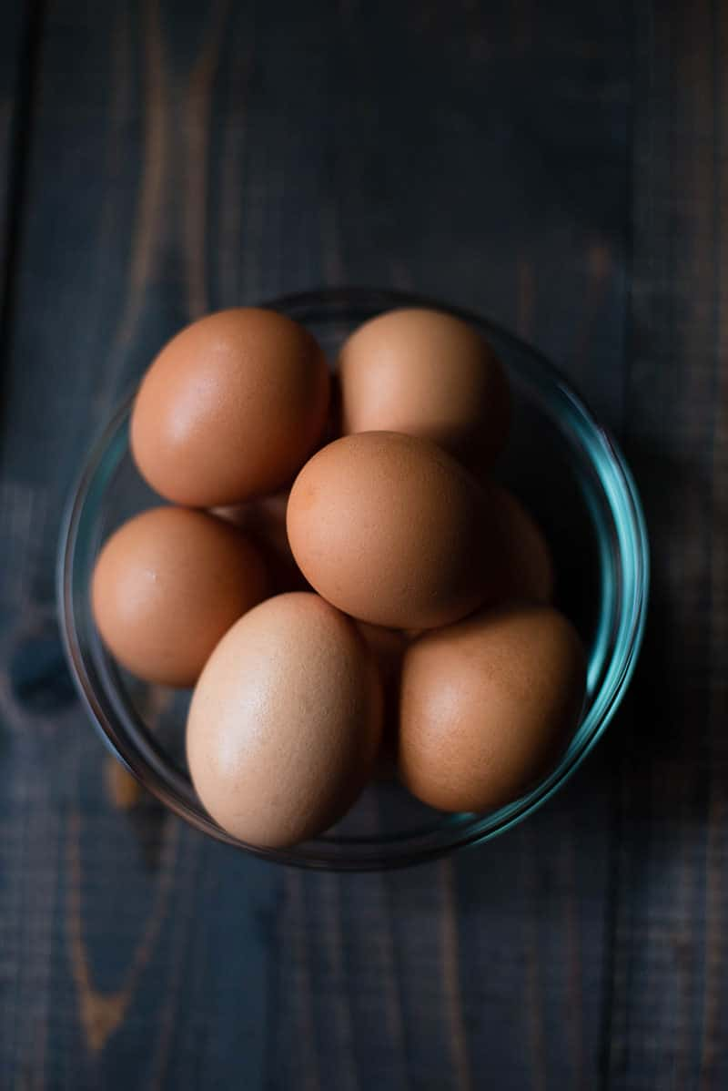 Overhead view of a blue bowl filled with brown shelled eggs.