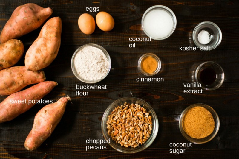 All the required ingredients to make easy sweet potato casserole separated on a counter, including the real sweet potatoes, eggs, buckwheat flour, chopped pecans, cinnamon, coconut oil, kosher or sea salt, vanilla extract, and coconut sugar.