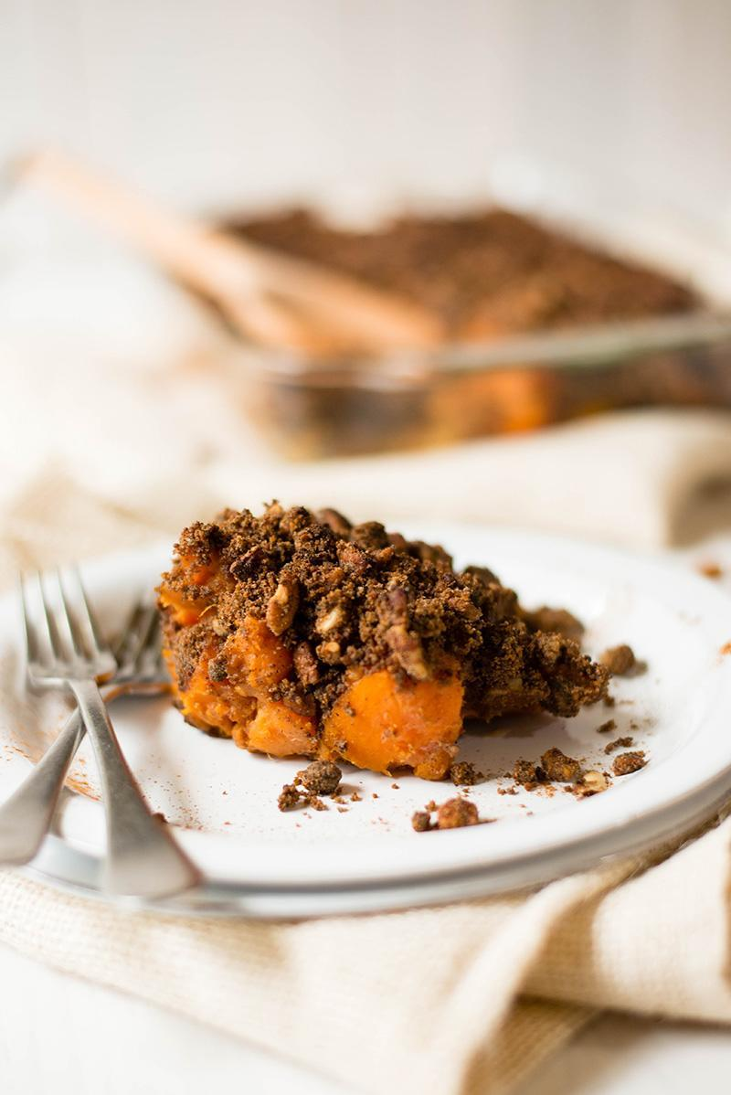 Close up photo from the side of one serving of the easy sweet potato casserole to show the cooked, sweet potatoes on the bottom and then topped with the crunchy coating.