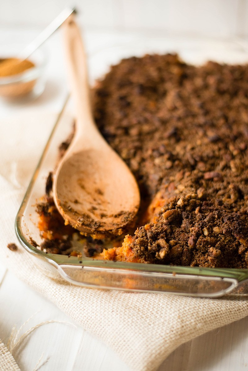 Casserole dish filled with the easy sweet potato casserole that has the crunchy pecan topping. A wooden spoon is setting on the casserole and a serving is missing from the dish.