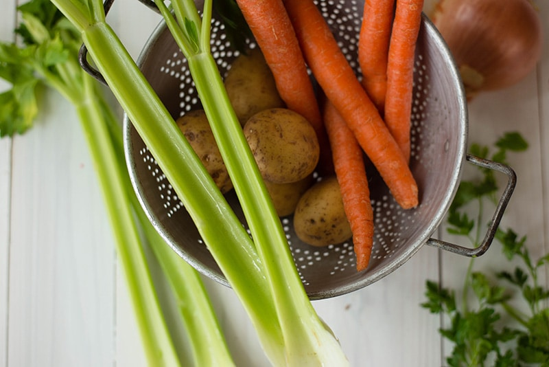 Overhead view of potatoes, carrots, and celery as examples of vegetables to eat to avoid 12 Weight Loss Mistakes.