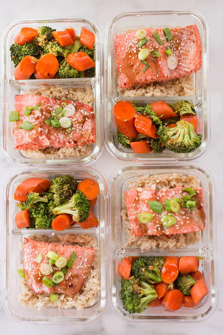 Overhead view of meal prep containers with teriyaki salmon, streamed brown rice, and teriyaki veggies.