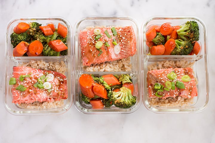 Three meal prep containers lined up showing teriyaki salmon meal prep along with teriyaki carrots and broccoli and steamed rice.