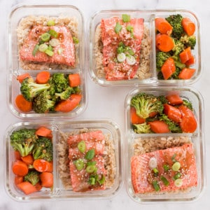Square image of 4 teriyaki salmon meal prep meals with steamed brown rice and teriyaki veggies.