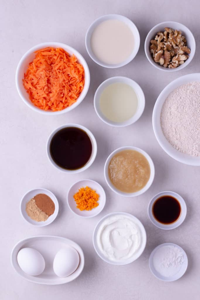 Overhead view of ingredients for Healthy Carrot Cake Cupcakes, including shredded carrots, spelt flour, spices, walnuts, and maple syrup.