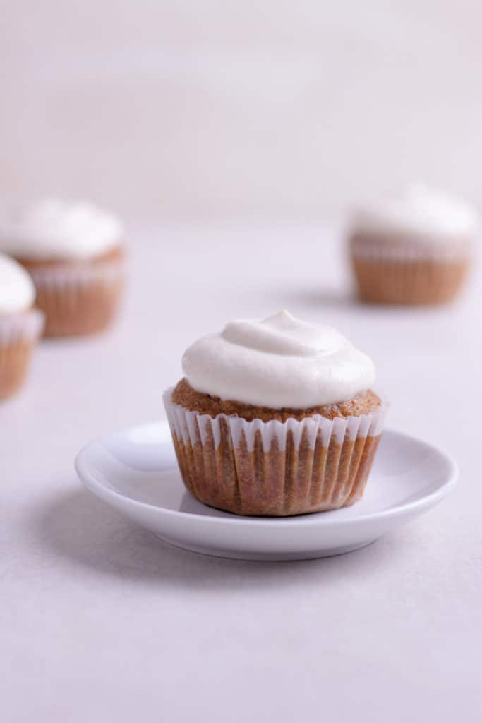 Close up side view of a Healthy Carrot Cake Cupcake iced and ready to eat, on a white plate, with other cupcakes in the background.