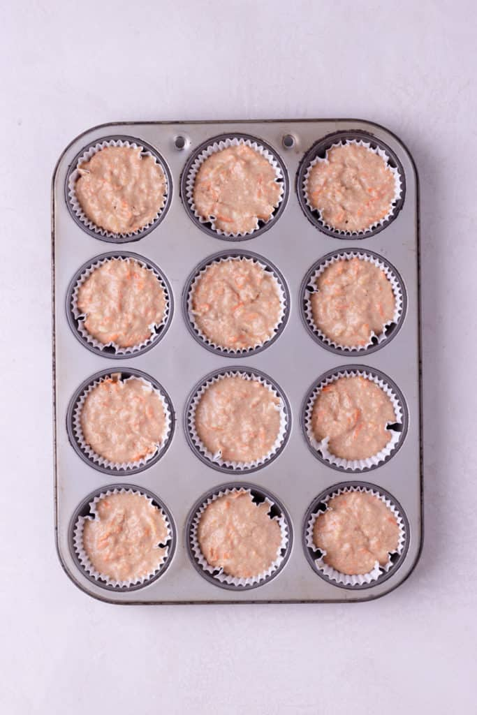 Overhead view of cupcake tins filled with Healthy Carrot Cake Cupcakes batter.
