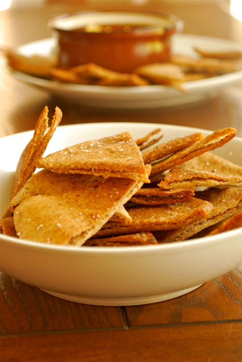 Side image of a bowl of homemade baked pita chips, with a large plate of chips in the background along with a bowl of dip.