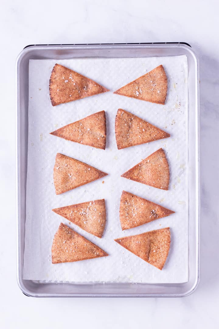 Overhead image of 10 pita triangles on a baking sheet, baked and ready to eat.
