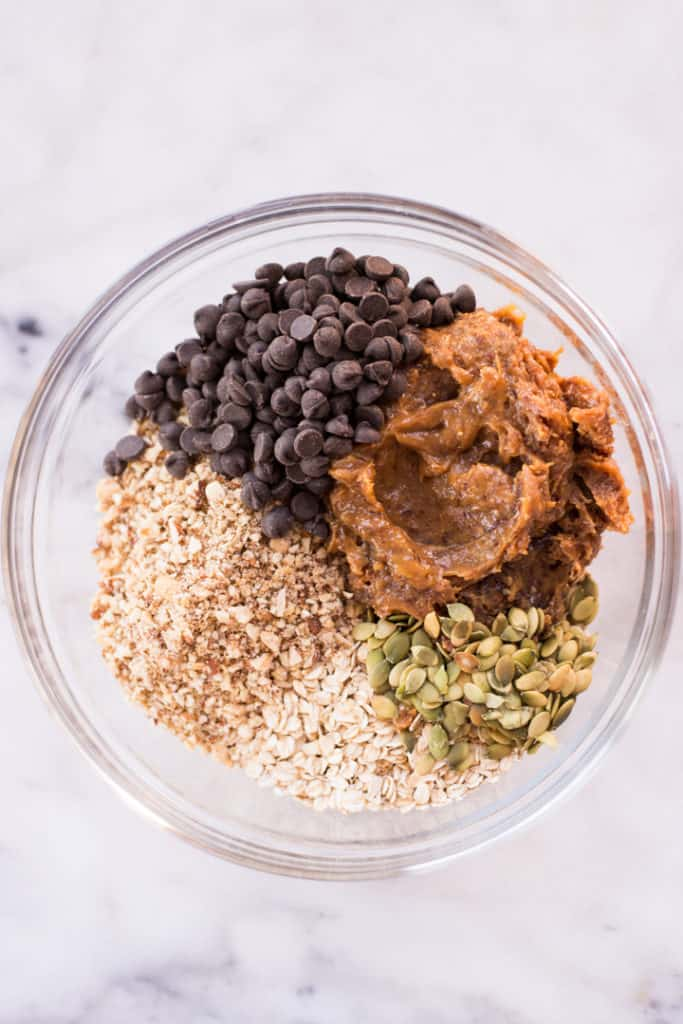 Overhead image of a glass bowl with ingredients for homemade protein bars, including oats, peanut butter, and pumpkin seeds.
