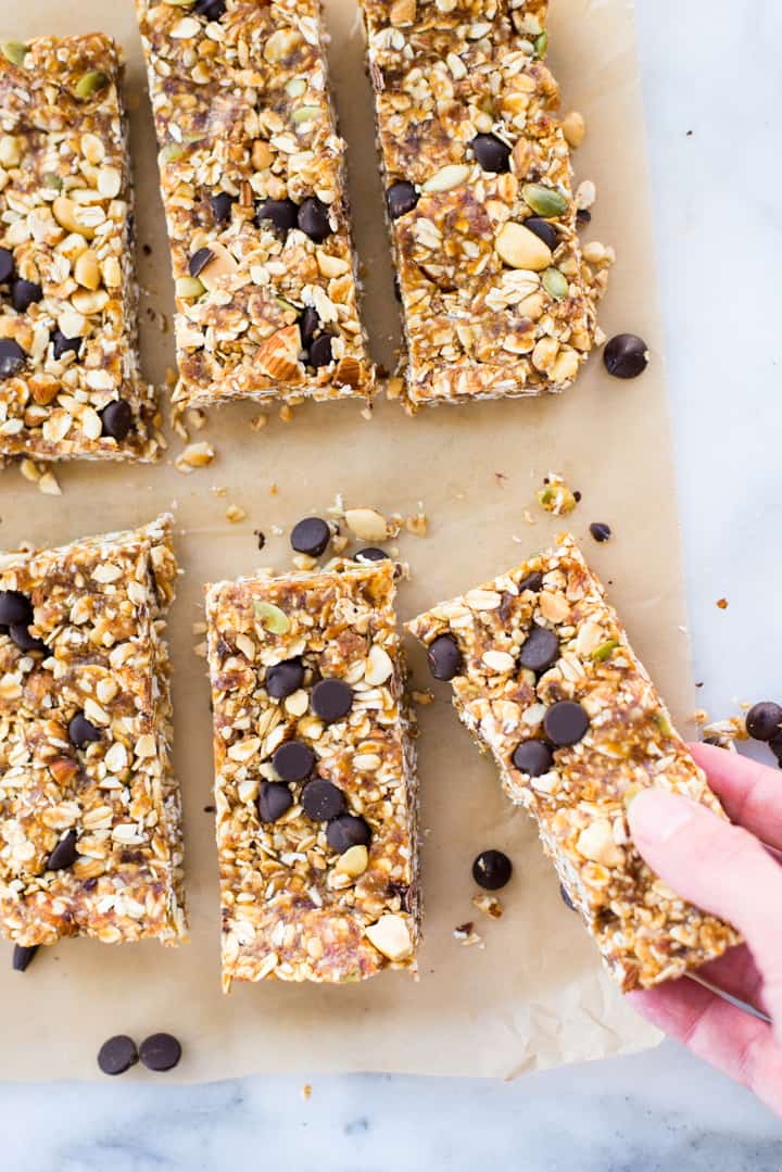 Overhead view of sliced Homemade Granola Bars on parchment paper, with a hand reaching for one of the bars.