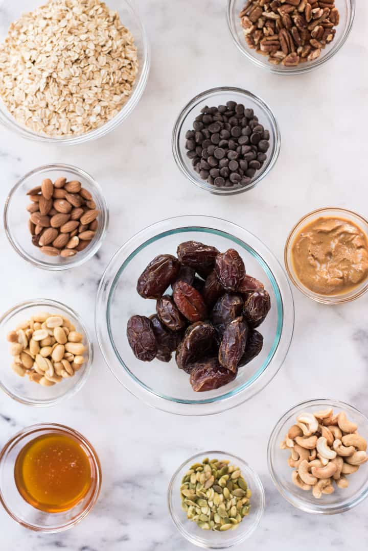 Overhead view of ingredients for Homemade Granola Bars, some of the ingredients being raw honey, pepitas, dates, chocolate morsels, peanut butter, and nuts.