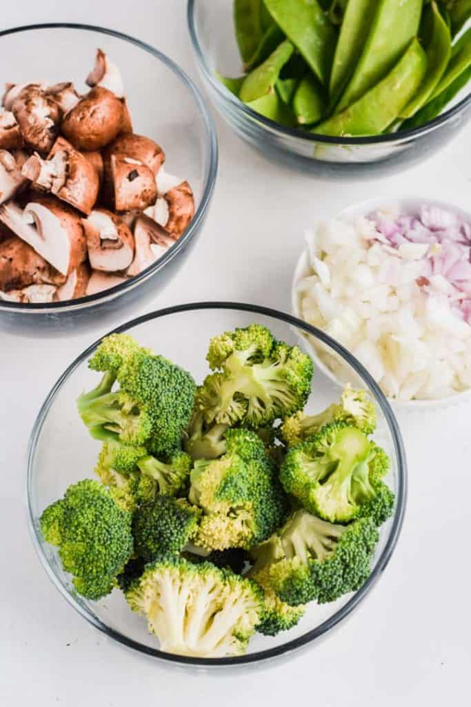 Overhead image of bowls containing ingredients for the Healthy Chicken Stir Fry including broccoli, mushrooms and onions.