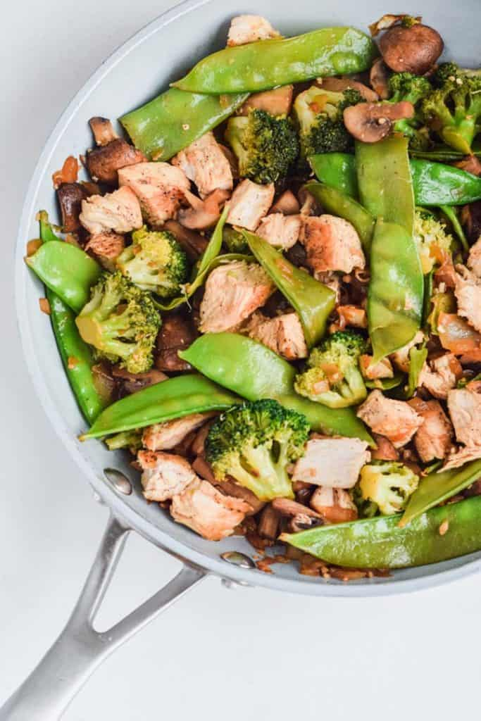 Overhead view of a skillet with the cooked stir fry, including chicken, snow peas, mushrooms, and broccoli.