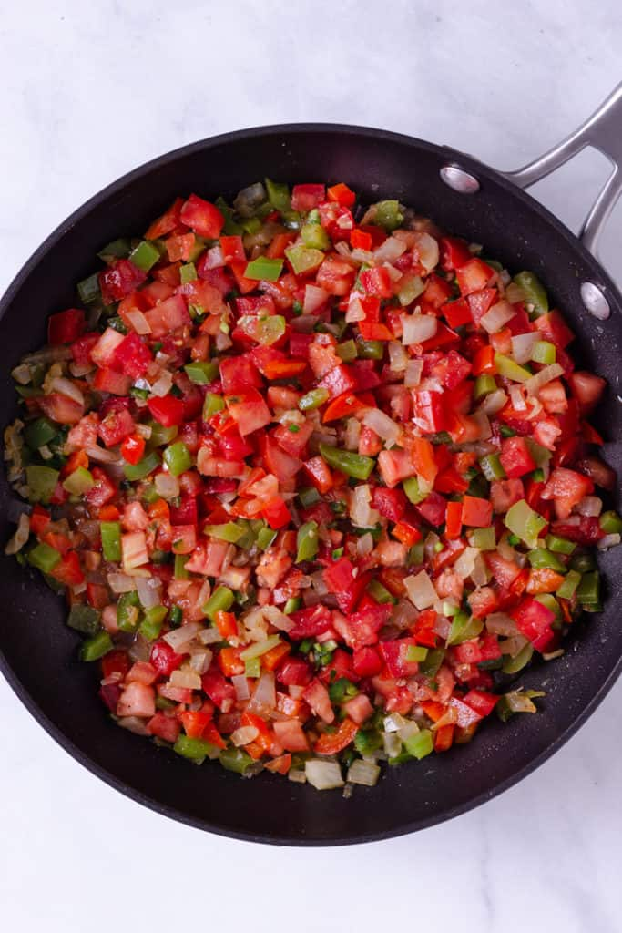 Overhead image of a skillet containing yellow onions, and red and green peppers chopped, as well as prepped plum tomatoes.