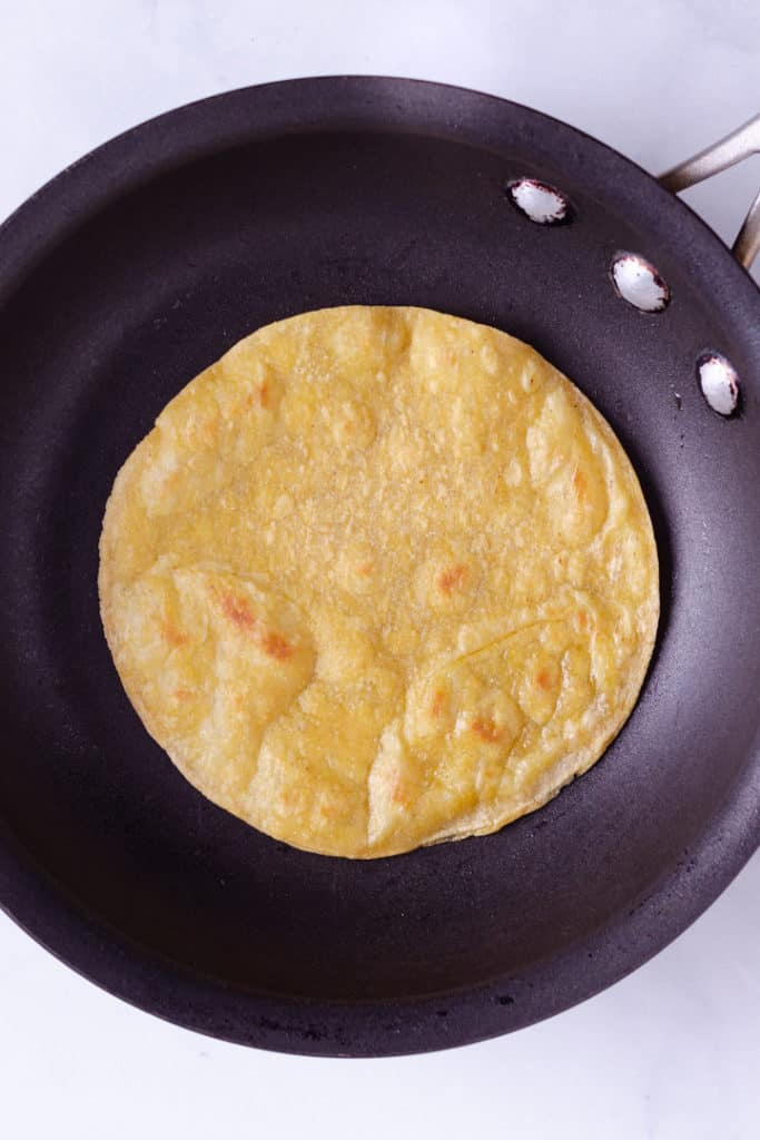 Overhead image of a corn tortilla in a skillet.