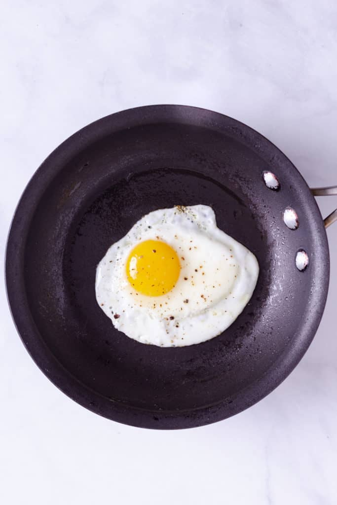 Overhead image of a sunny side up fried egg in a skillet.