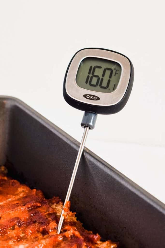 Close up view of an instant-read thermometer reading 160 F being inserted into cooked meatloaf.