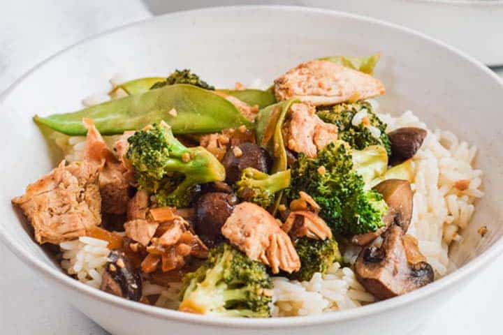 Close up side view of a bowl of Healthy Chicken Stir Fry, ready to eat.