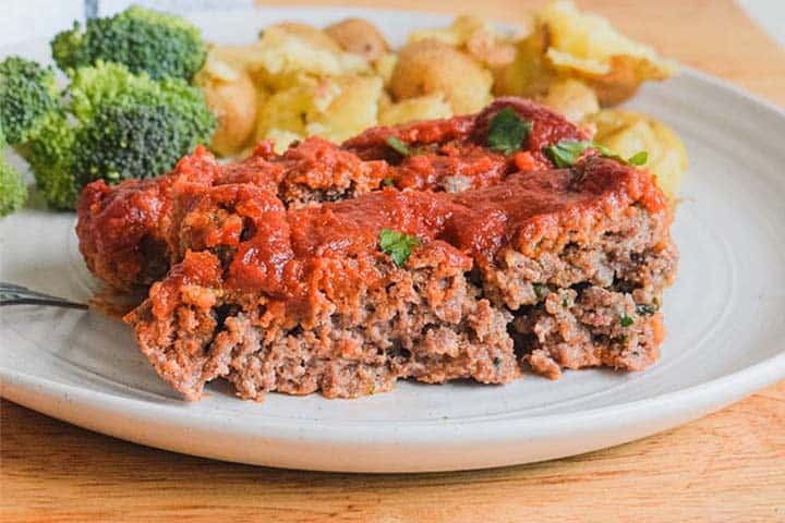 Side view of a white plate with meatloaf, broccoli and potatoes.