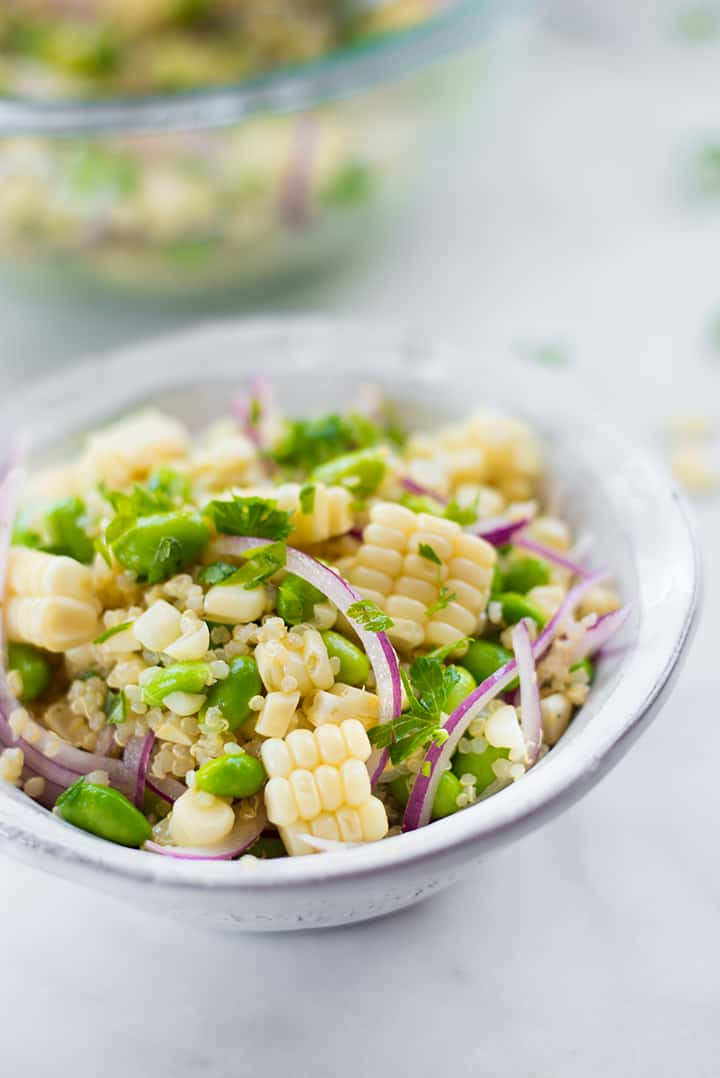 Side view of summer corn edamame salad, filled with cooked quinoa, sliced red onions, edamame, and fresh corn.
