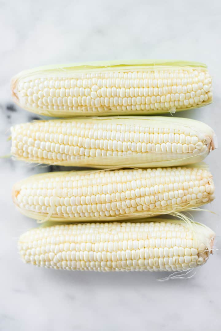 Fresh ears of corn, ready to be cooked for the Summer Corn Edamame Salad