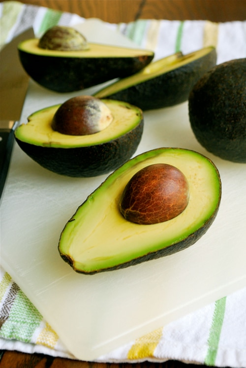 Side view of avocado halves with the pits not yet removed, sliced and ready to use in recipes.