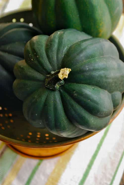 Fresh acorn squash that are ready to be sliced in half and roasted to make the roasted acorn squash soup.