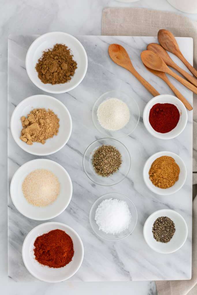 Overhead image of a marble cutting board with white and clear bowls filled with spices including paprika, cumin, kosher salt, dried oregano, ground ginger and more; wooden spoons are beside.