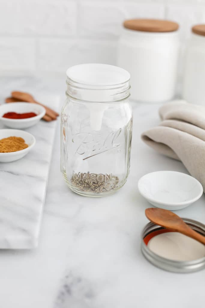 Close up side view of a mason jar containing a few of the ingredients to make taco seasoning mix, with some of the spices pictured beside.