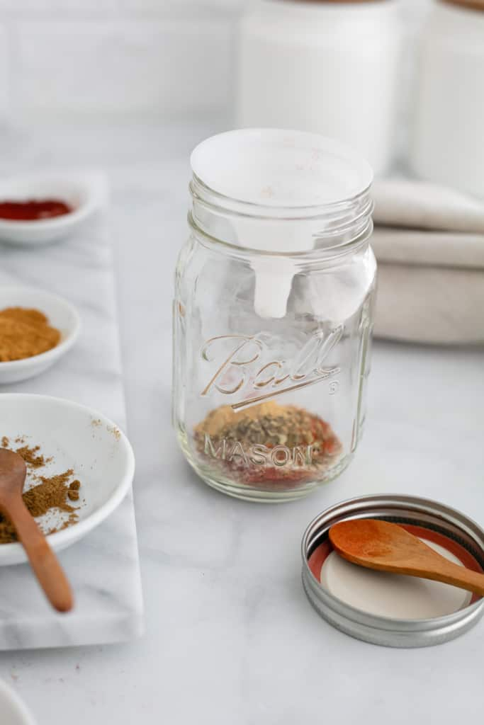 A side view of some of the spices in bowls; a bit of the mixture is in a bowl with a wooden spoon and a funnel is in the mason jar for adding the mix.