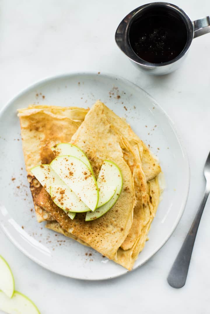 Overhead image of two Homemade Healthy Crepes on a white plate, topped with apples and cinnamon and with a serving of pure maple syrup beside it.