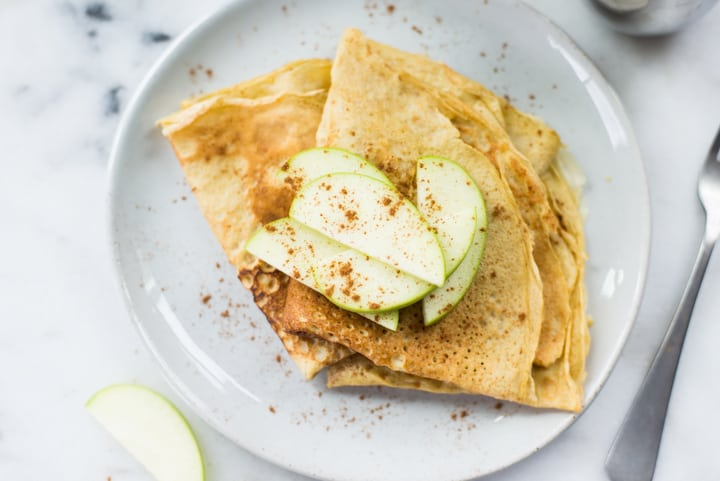 Overhead view of a white plate containing two folded over Homemade Healthy Crepes that are topped with green apple slices and cinnamon.