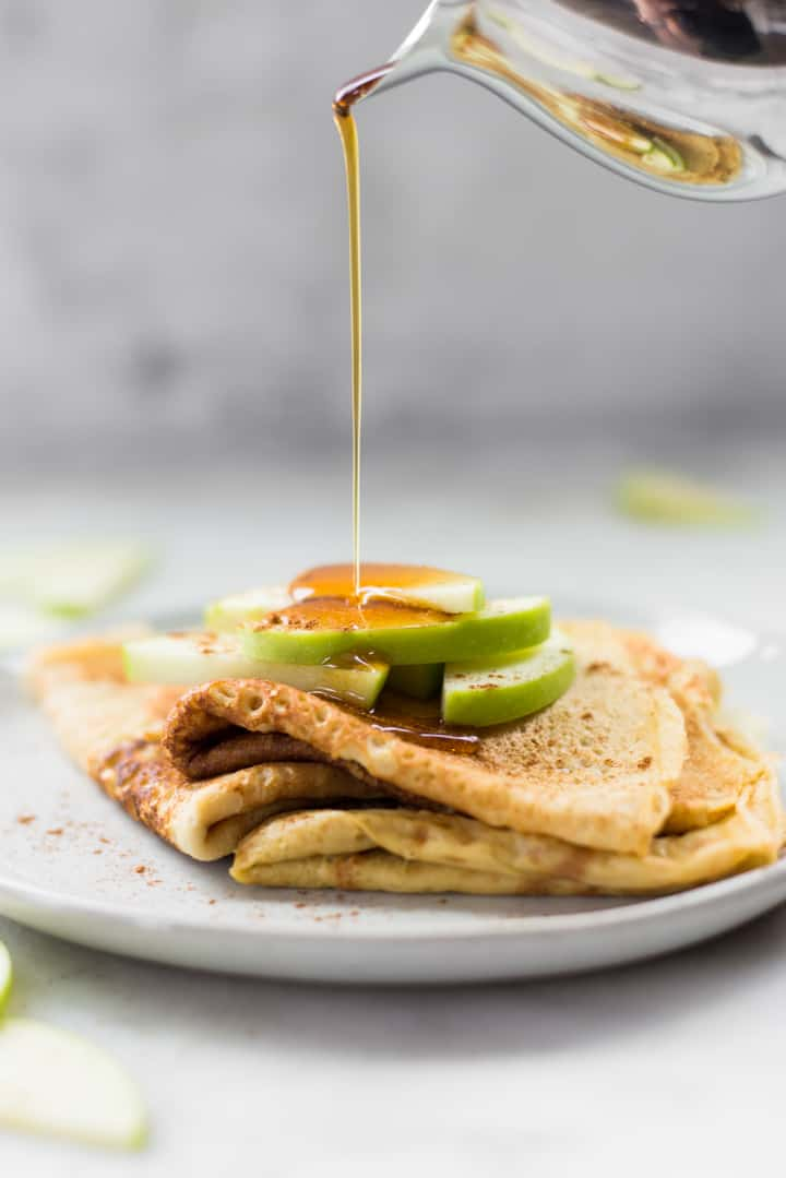 Side view of pure maple syrup being poured on a plate of Homemade Healthy Crepes topped with apple slices and cinnamon.